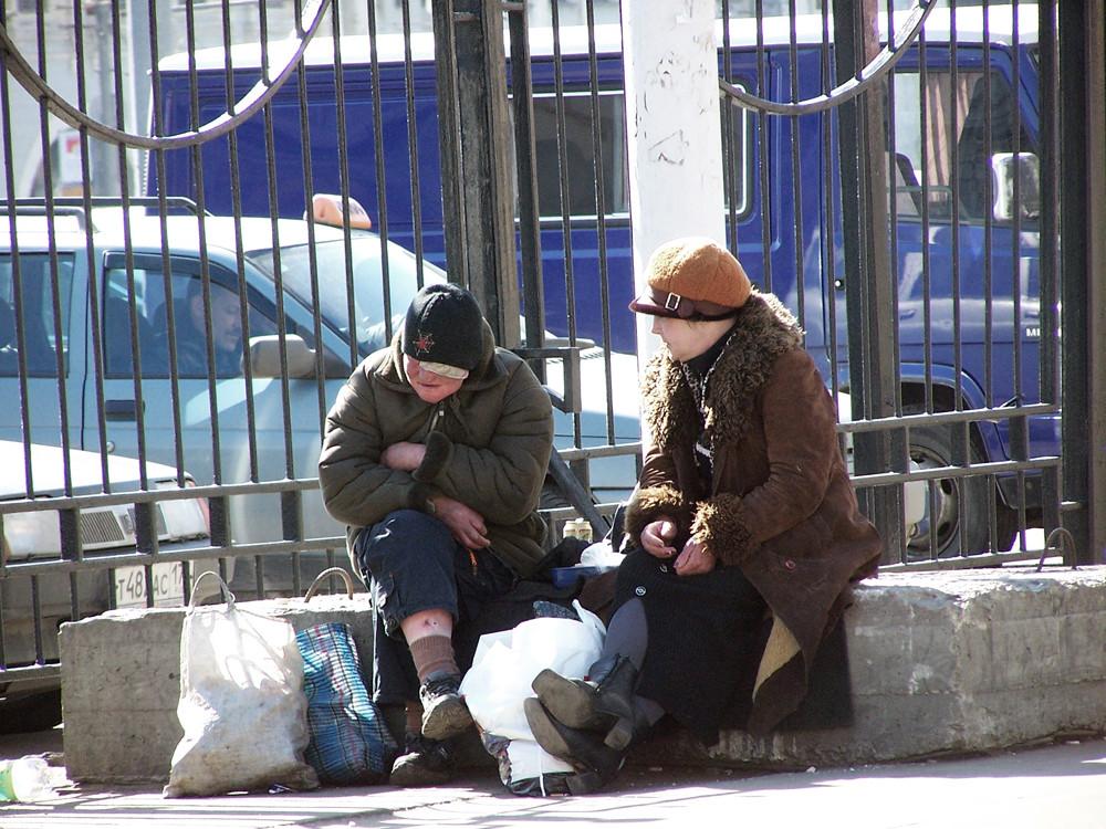 Lesender Taxifahrer hinter Gittern und zwei älteren Frauen mit Taschen auf Betonblock