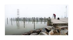 Leuchtturm im Nebel und Fotograf bei der Arbeit