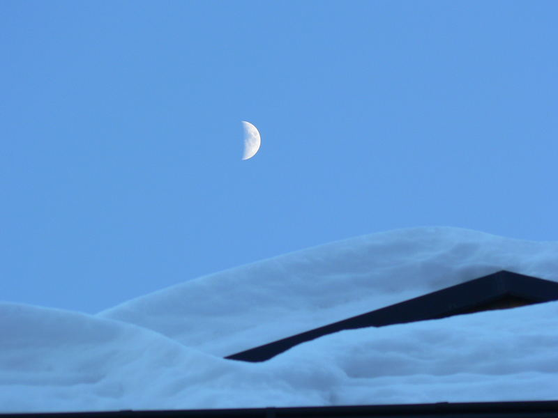 Luna sopra tetti innevati