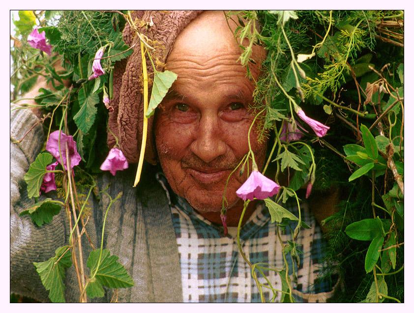Mann mit Blumen auf dem Kopf