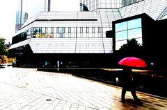 Mann mit rotem Schirm kommt aus der Deutschen Bank