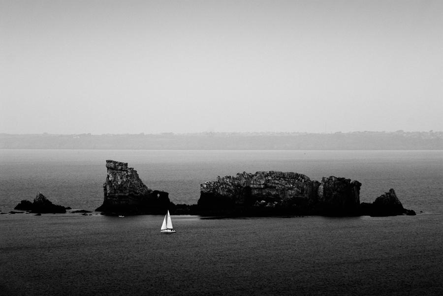 menschen in der freizeit auf einem schiff vor einer insel bei leichtem wind und geringem seegang