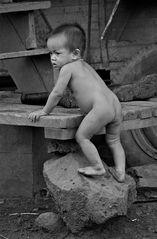 mit stiefeln spielendes kind in einem bergdorf