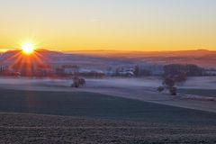Morgensonne über dem Nebel der Nacht auf den Wiesen und Feldern