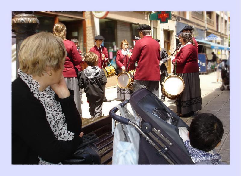 mujer con niño mirando una banda musical