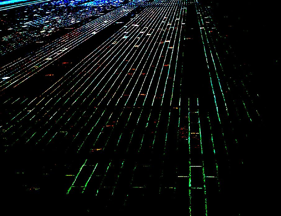 NEW YORK CITY AT NIGHT, AS SEEN THROUGH THE COCKPIT OF A JET ABOUT TO LAND