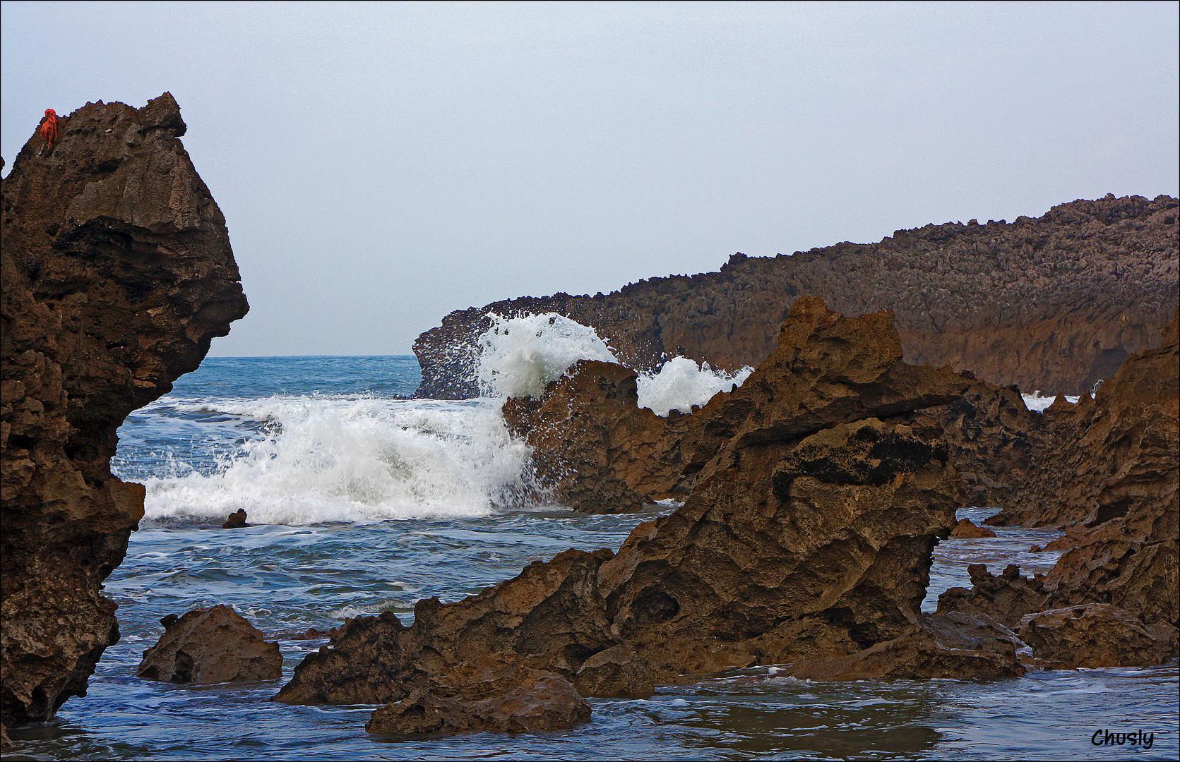 Ola rompiendo contra las rocas