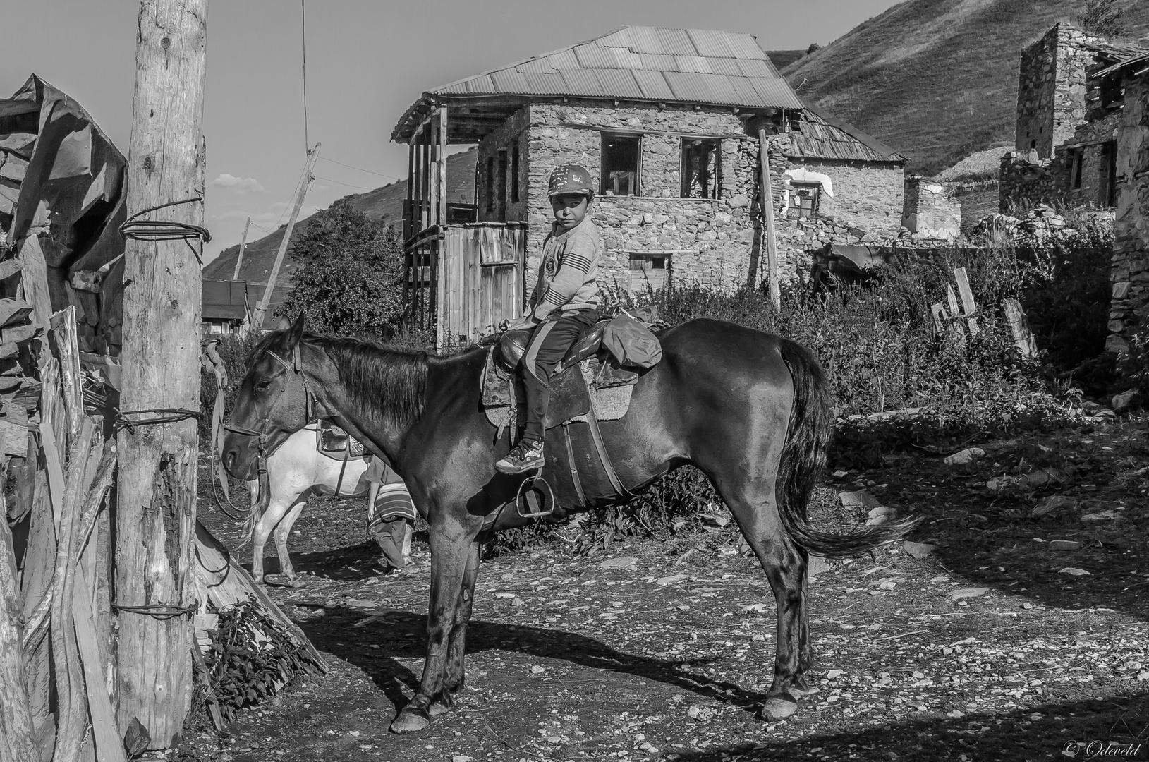On horseback.