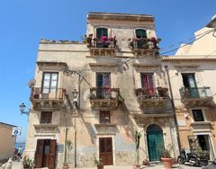 Ortigia e le sue vecchie case con i balconi addobbati di fiori, segno di una vitalità ritrovata.