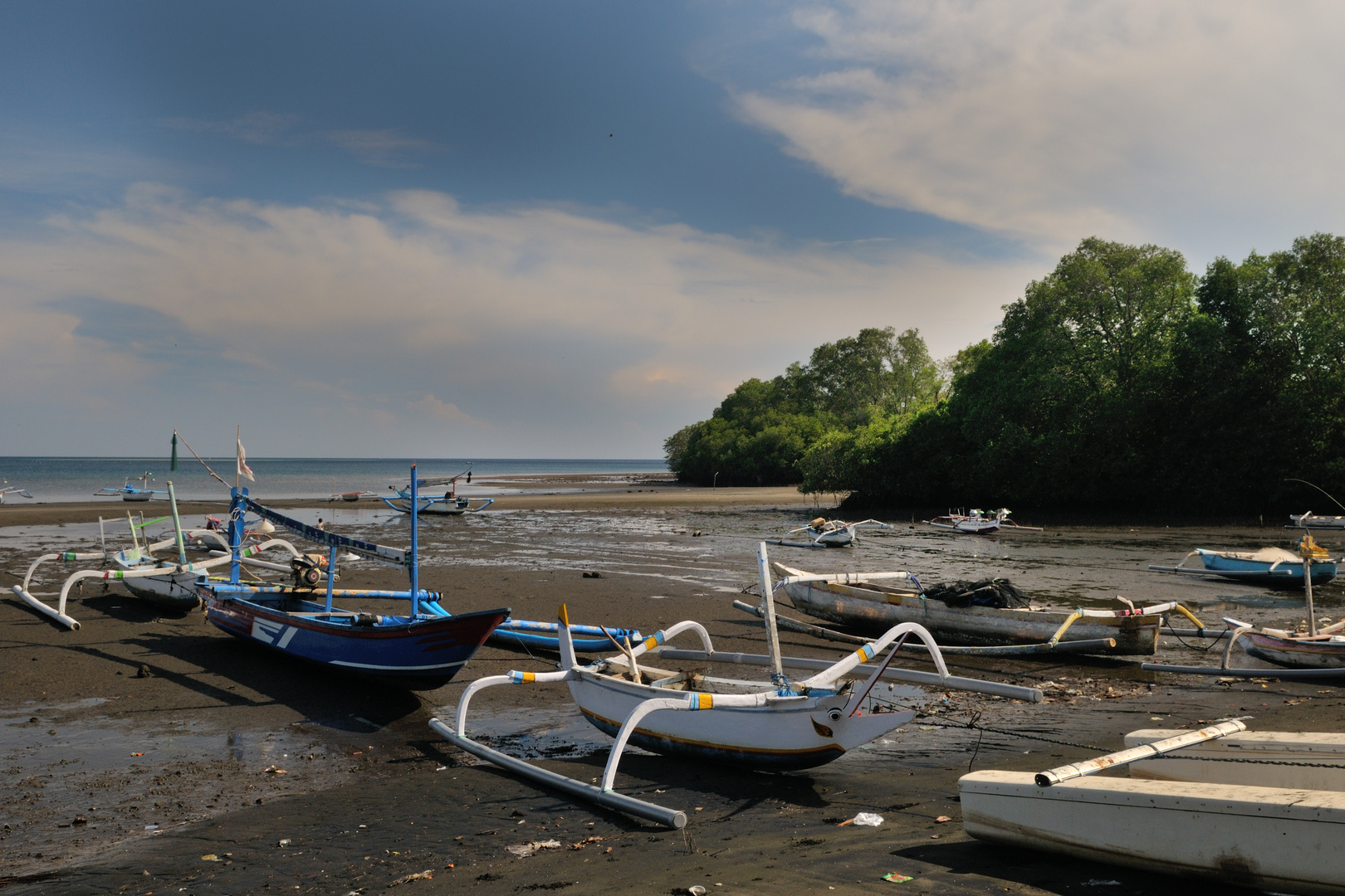Outrigger boats stranded on low tide