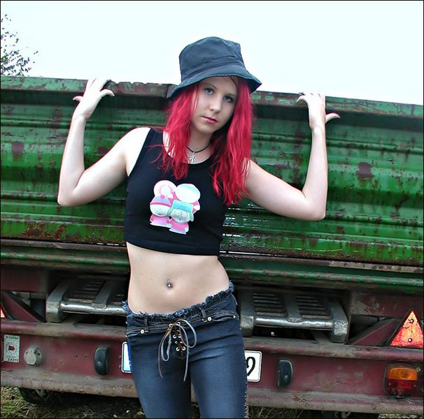 Pale Beauty with red hair and a green rusty truck