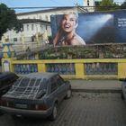 Plakat und parkende Autos in Cachoeira aus dem Bus fotografiert