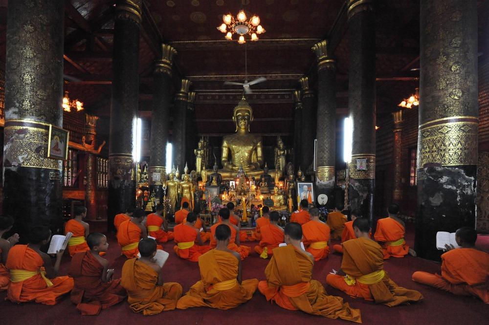 Praying in Wat Mai Souwannaphumaham