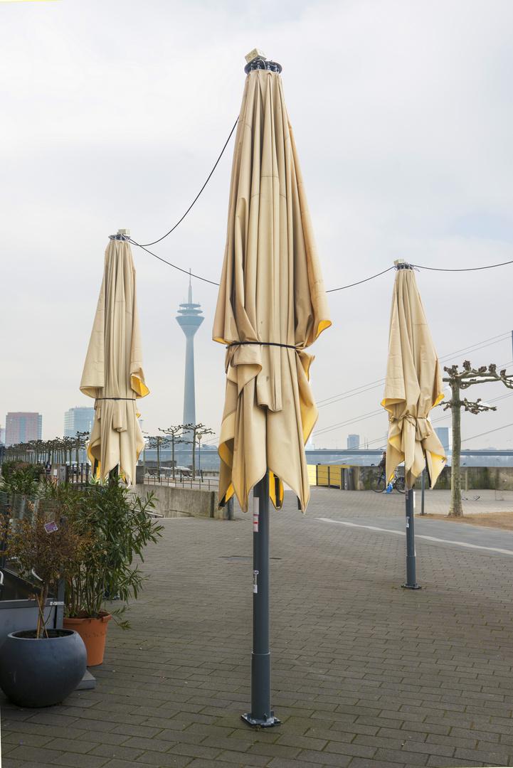 Rheinpromenade mit Rheinturm und Sonnenschirmen