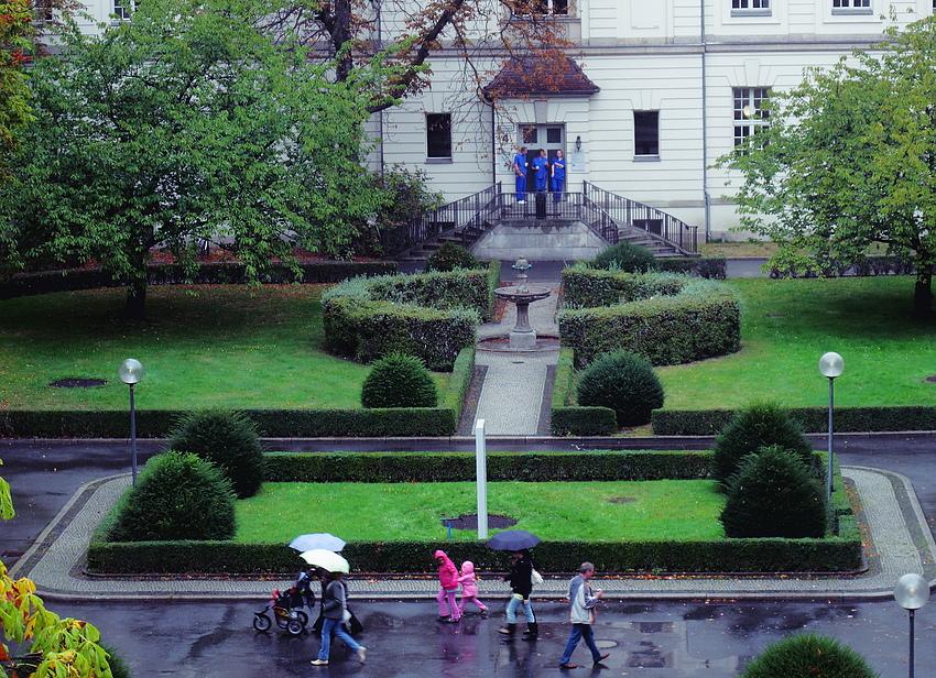 Rosa Kinder und blaue Pfleger im Regen