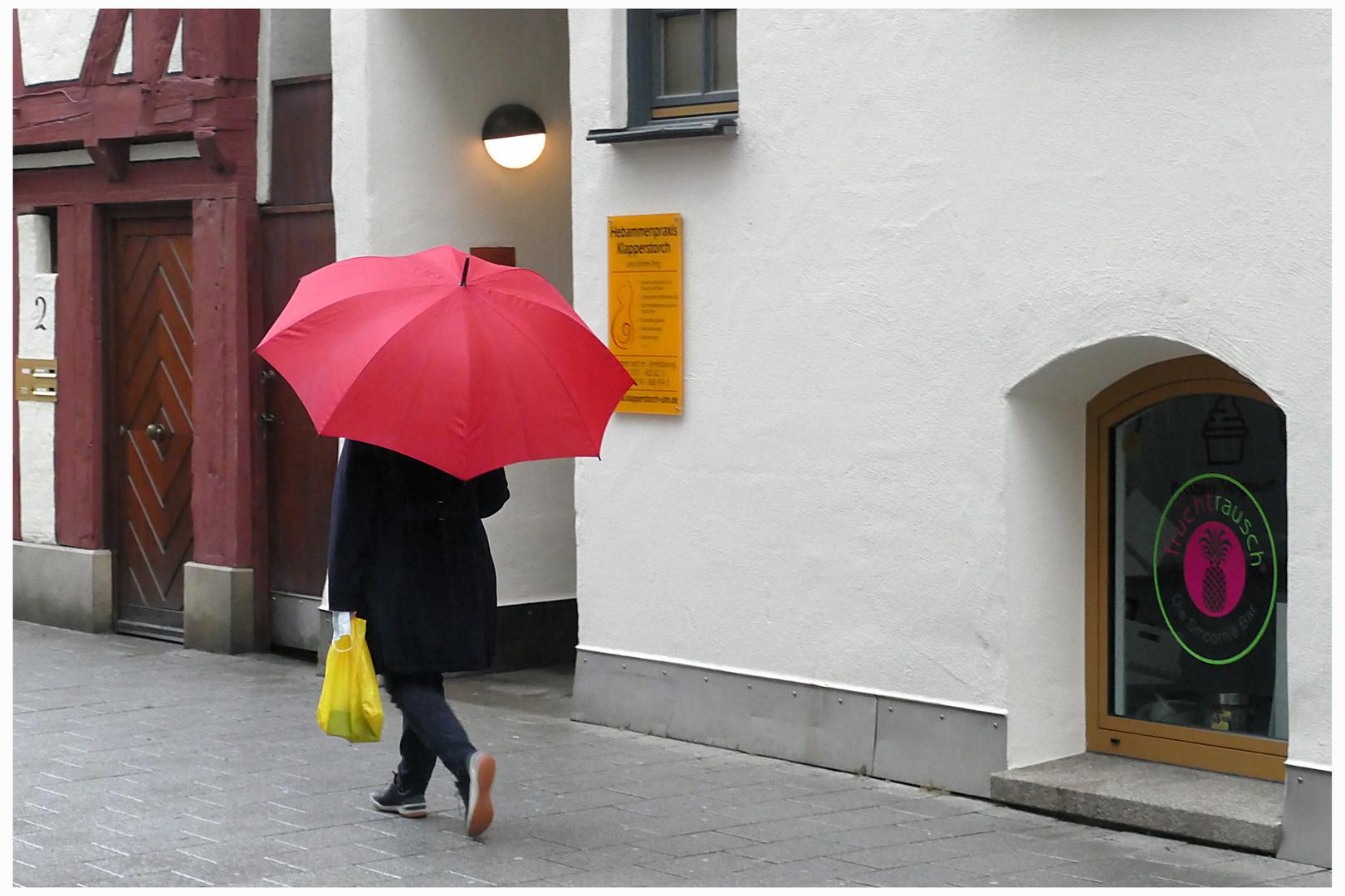 Roter Schirm und gelbe Tüte