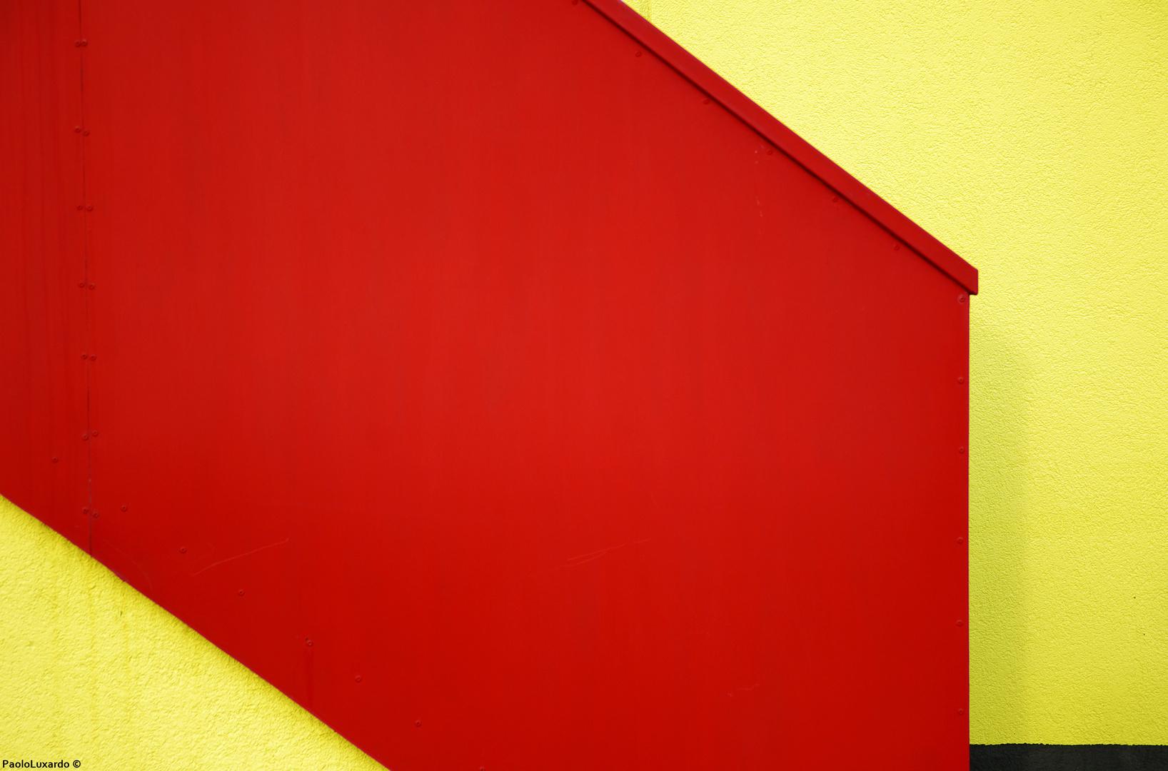 scala rossa su muro giallo