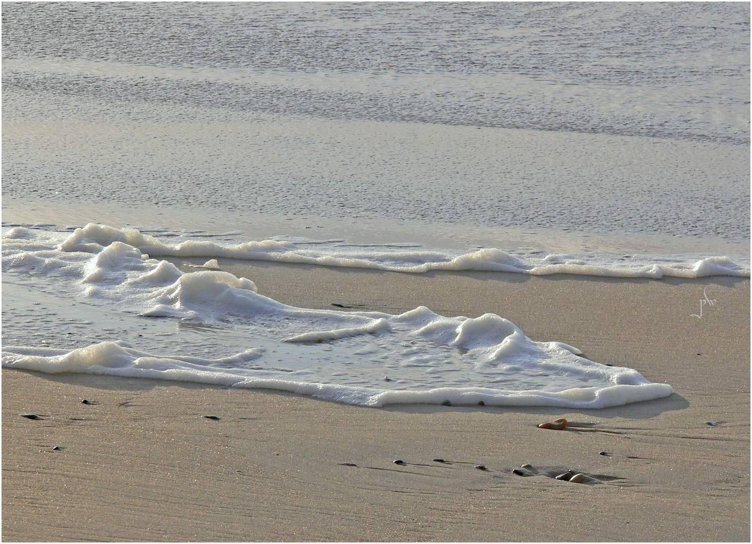 Schaumzungen, die - durch Sturm erzeugt - über den Strand kriechen