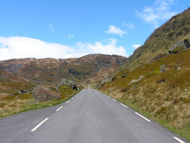 Schnurgerade Strasse durch ein Tal, Serpentinen den Berg hinauf