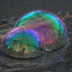 Seifenblasen mit Spiegelwirkung auf gefrorenem Gartenteich