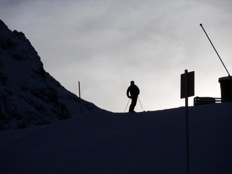 Skifahrer am Abend auf dem Gipfel