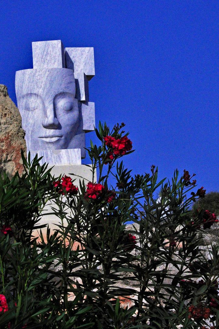 Skulptur unter Blumen