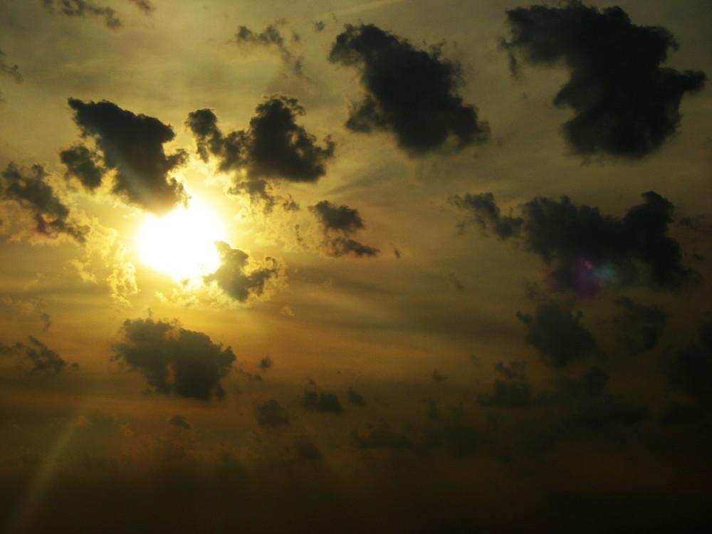 Sonne hinter versteckten schwarzen Wolken