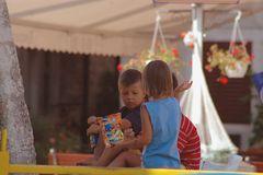 Spielende Kinder im Schatten eines Kirchturmes.