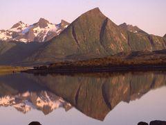 Spitze Berge spiegeln sich bei Sonnenschein auf den Lofoten