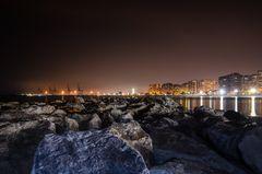 Steinmole am Strand von Malaga vor der nächtlichen Skyline der Stadt