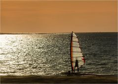 Surfer im Sonnenuntergang am Meer