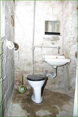 Toilettenraum aus der Nachkriegszeit mit neuzeitlicher Klobürste