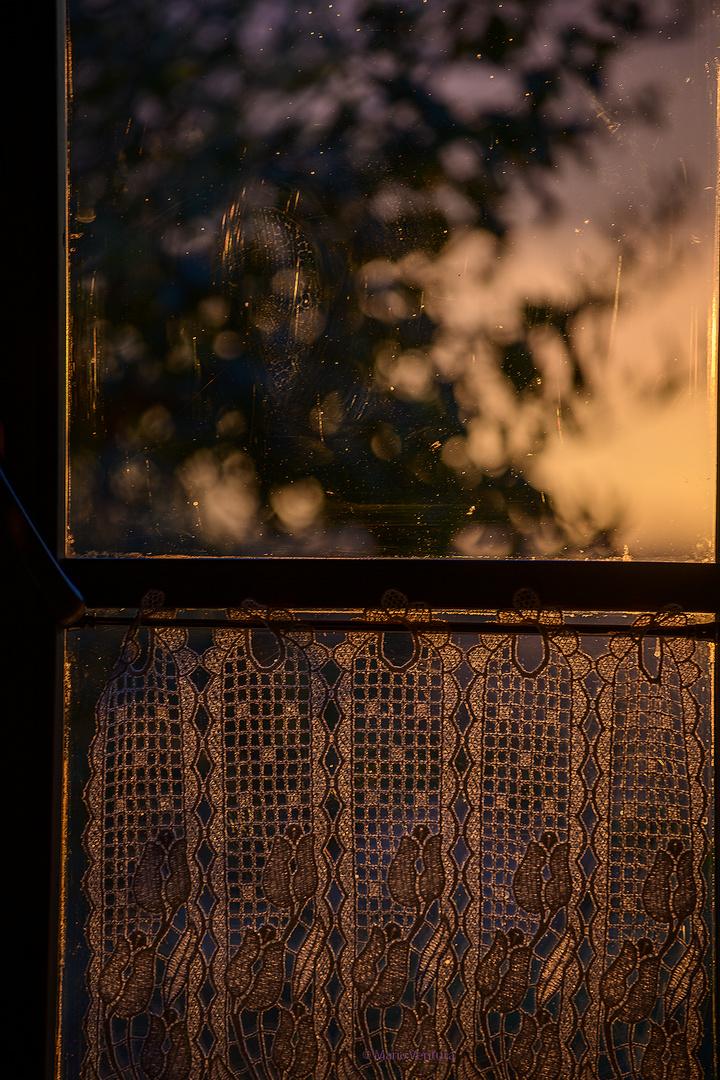 Tramonto da una finestra chiusa