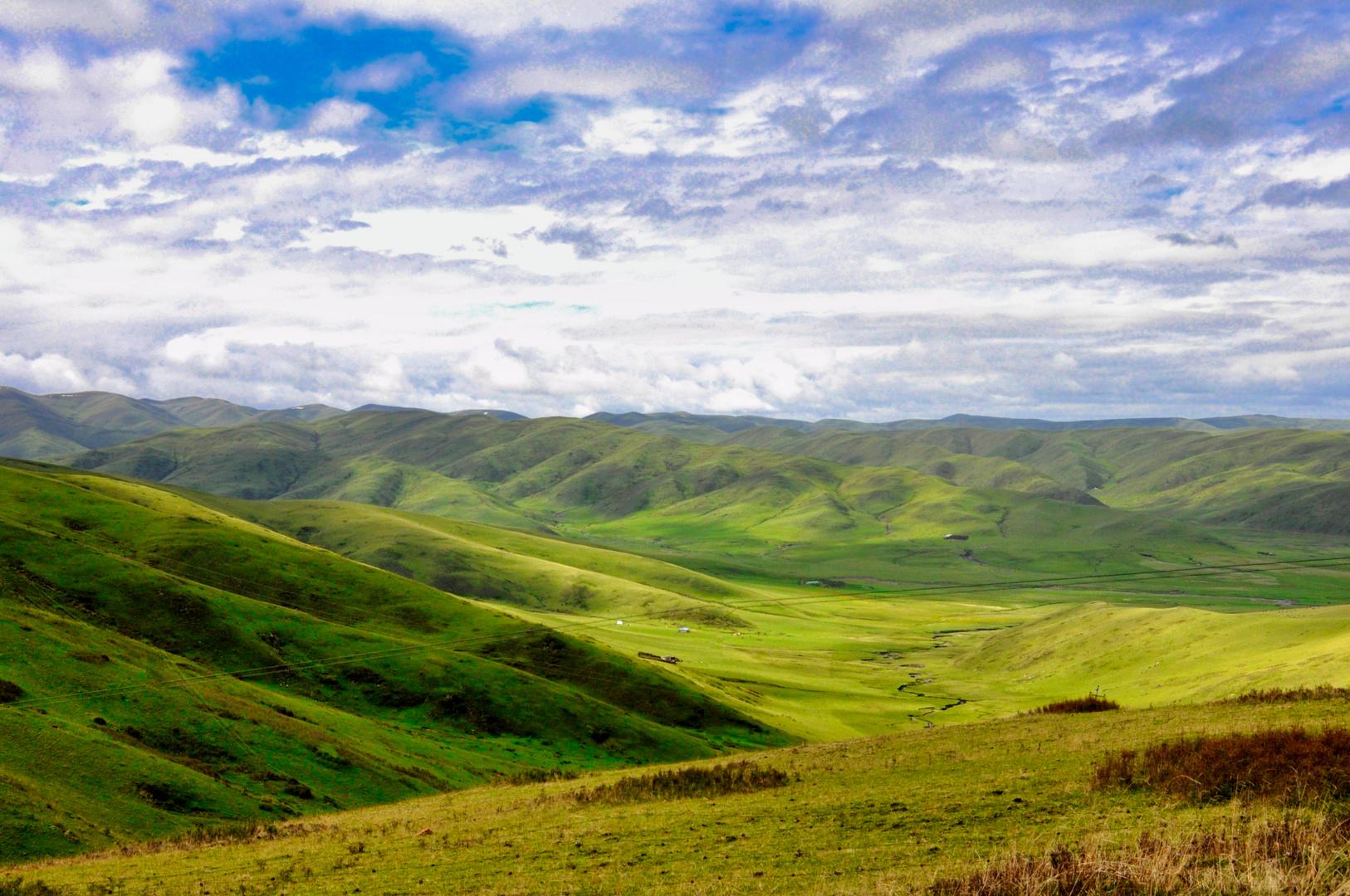 Traumlandschaft Osttibet Sichuan grüne Wiesen blau-weißer Himmel