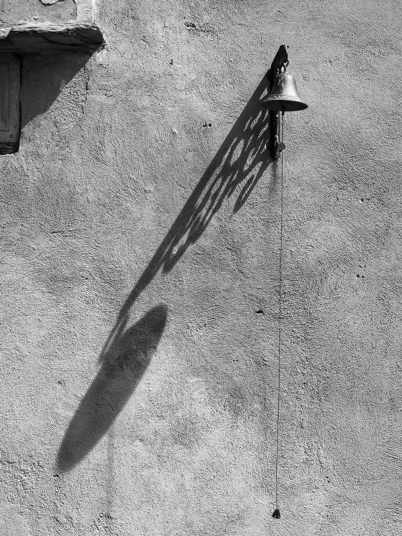 Türglocke vor einer Wand und Schattenwurf