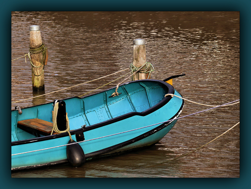 Turquoise boat in brown water