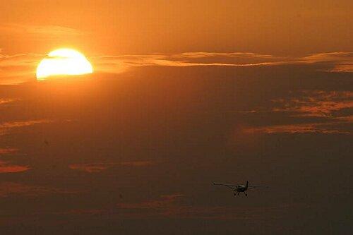 UL-Flugzeug vor Abendsonne