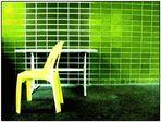 Unbequemer Plastikstuhl von Mann in geschmacklosem Hemd vor giftgrüner Wand drapiert