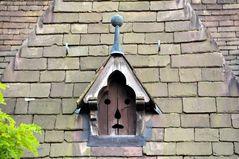 ungläubiges Gesicht ziert kirchliche Dachgaube