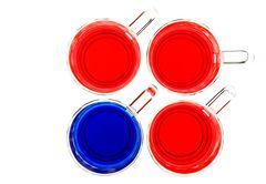 Vier Glas-Tassen mit farbigem Wasser