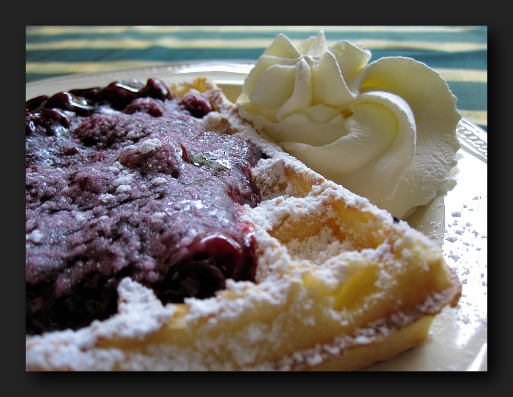 Waffle with hot sour cherries and whipped cream