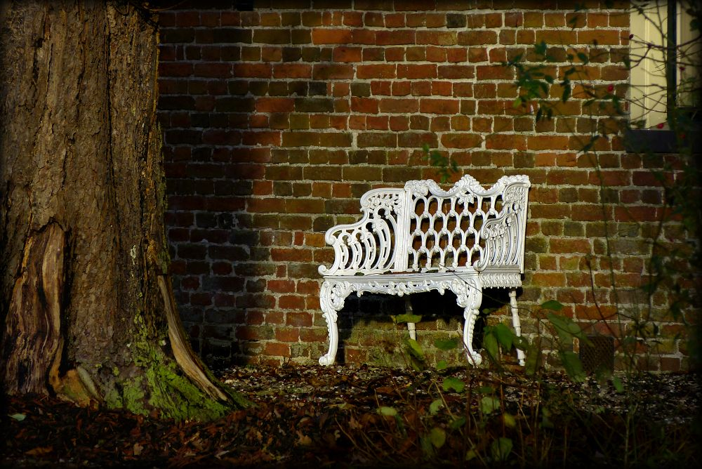 White bench near the old stone wall