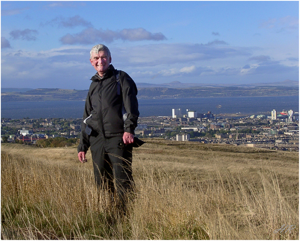 Windzersaust auf Arthurs Seat mit Edinburgh im Rücken