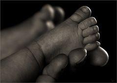 Zarter Fuß in starker Hand