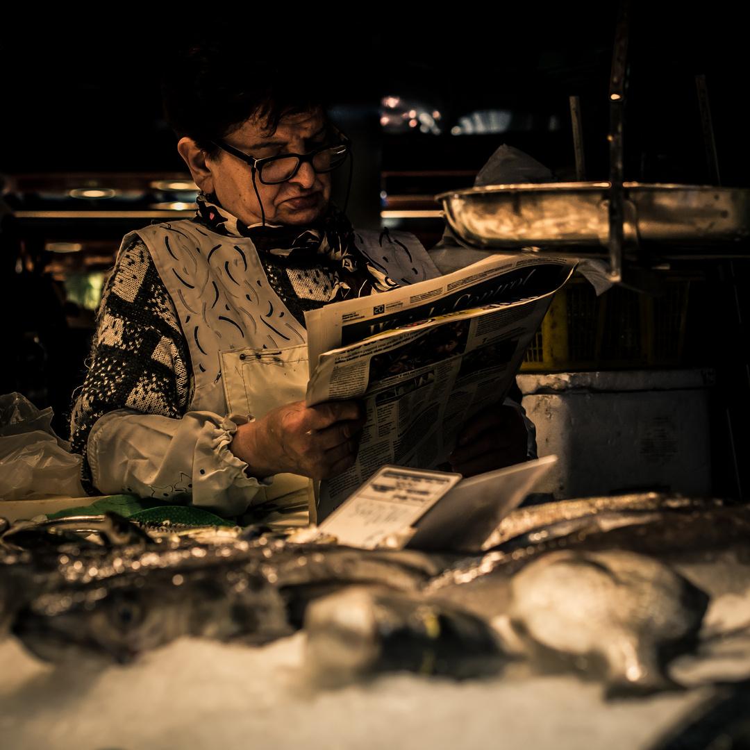 Zeitunglesende Fischverkäuferin