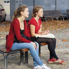 Zwei in rot auf einer Bank